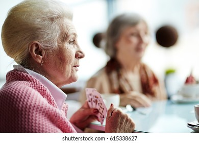 Head and shoulders portrait of beautiful senior woman having tea party in lovely cafe and playing cards with her best friend