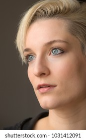 Head and shoulders portrait of  beautiful young woman with short blonde hair looking aside in window light.