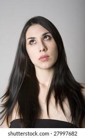 Head and shoulders portrait of brunette woman rolling her eyes upward