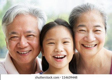 Head And Shoulders Portrait Of Chinese Grandparents With Granddaughter Ride