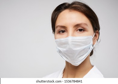 Head and shoulders portrait of female doctor wearing protective mask and looking at camera posing against white background, copy space