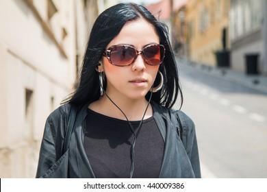 Head and shoulders portrait of girl in black coat, sun glasses and earphones listening music