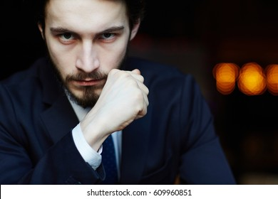 Head and shoulders portrait of handsome bearded man wearing elegant business suit, looking strongly at camera with powerful hand gesture