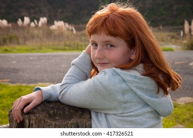 head and shoulders portrait  of little red haired girl looking over her shoulder towards camera natural lighting outdoors