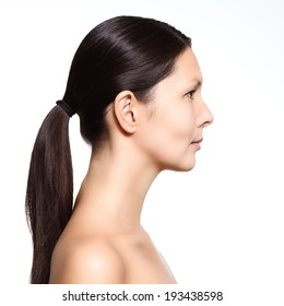 Head and shoulders portrait of a naked young woman with a serious expression standing in profile with her long brown hair neatly tied in a pony tail revealing her graceful long neck isolated on white