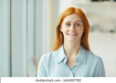 Head and shoulders portrait of red haired businesswoman smiling at camera while standing by window in modern white office, copy space