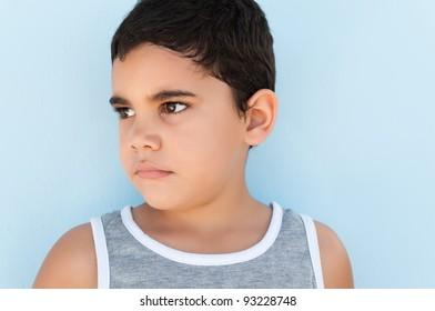 Head and shoulders portrait of a sad latin kid
