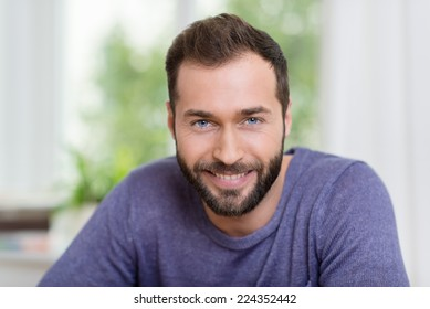 Head and shoulders portrait of a smiling bearded man looking at the camera with a friendly smile, indoors at home
