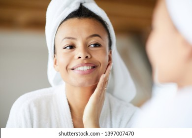 Head and shoulders portrait of  smiling Mixed-Race woman looking in mirror during morning routine, copy space - Shutterstock ID 1397007470