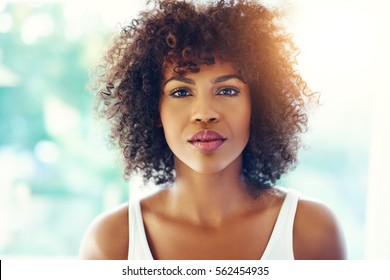 Head and shoulders portrait of thoughtful young black woman in bright sunshine