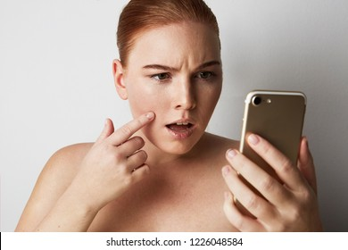 Head and shoulders of redhead woman with natural makeup. Disappointed girl looking at mobile phone sadly and pointing finger pimple on skin