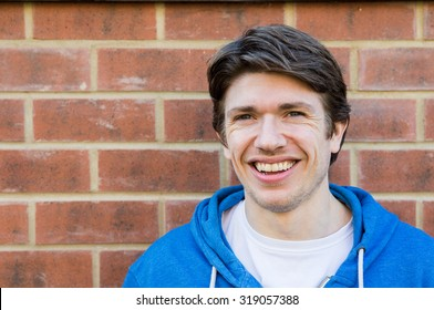 Head and shoulders shot of a young man, 25-30, stood against a brick wall.  He has blue eyes, and brown hair, styled in a parting.  He is smiling.