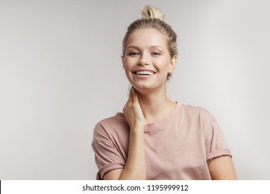 Head and shoulders studio portrait of beautiful young caucasian blonde woman, with perfect skin and toothy smile. Youth and Skin Care Concept. Isolated over white background