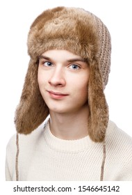 Head and shoulders studio portrait of smiling teenager boy wearing brown knitted faux fur winter trapper hat (Ushanka) and sweater on white background