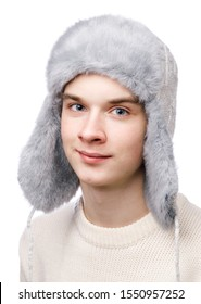 Head and shoulders studio portrait of smiling teenager boy wearing blue knitted faux fur winter trapper hat (Ushanka) and sweater on white background