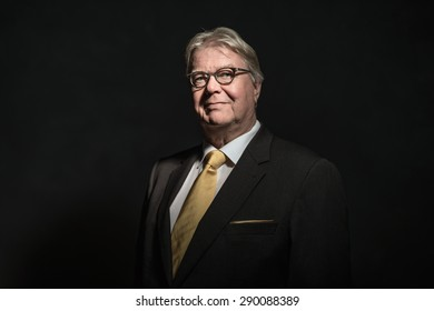 Head and shoulders of a stylish middle-aged businessman wearing eyeglasses looking at the camera in a dark room with light falling on his face