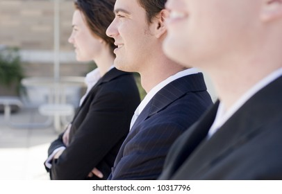 head and shoulders of three business people looking in same direction smiling