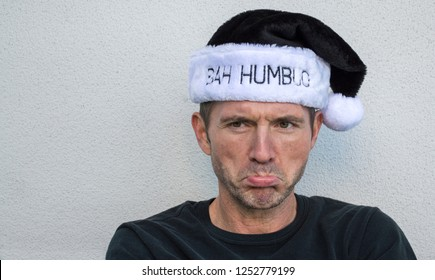 head and shoulders view of a handsome Caucasian man pouting while wearing a black and white  hat with the words Bah Humbug on it with copy space