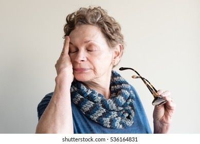 Head and shoulders view of older woman in blue clothing rubbing eyes and holding glasses (selective focus)