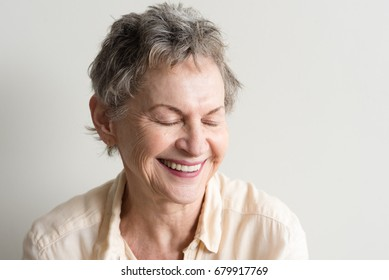 Head and shoulders view of older woman with short grey hair laughing with eyes closed against neutral background (selective focus)