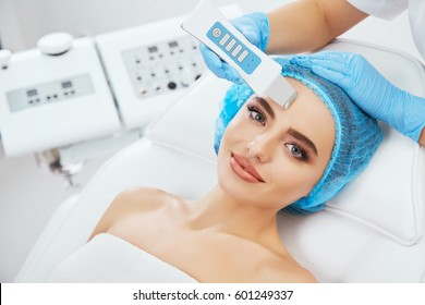 Head and shoulders of woman lying on couch in blue cap in cosmetological clinic and looking at camera. Doctor's hands in blue gloves holding ultrasonic scraber near her face