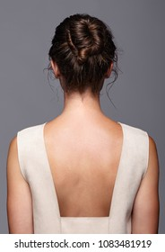 Head and shoulders of a young woman from the back side. Female hair knotted.