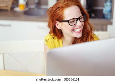 Head and Shoulders of Young Woman with Red Hair Wearing Eyeglasses and Laughing Joyfully While Working on Computer with Over-Sized Monitor at Home in Kitchen