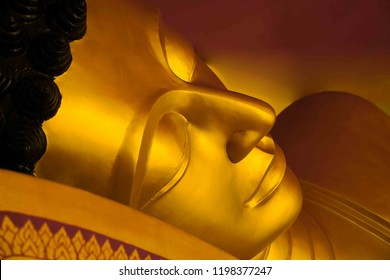 The head of a sleeping Buddha.The face of the golden Buddha statue.The face of a Buddhist statue made of brass metal.
