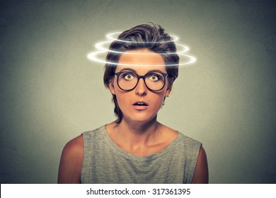 Head is spinning. Surprise astonished woman. Closeup portrait woman looking surprised in full disbelief open mouth isolated on grey wall background. Human emotion face expression body language.