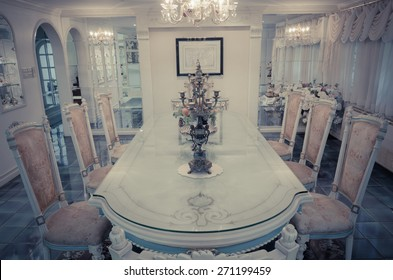 Head of the table with chairs in the grand dinning room interior architecture design of a residential house home in old vintage retro style similar to a European royal palace.