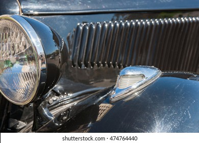 Head and turning lights of a vintage car of black color. You can see also part of a motor hood and a splasher or fender. Retro car.