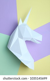 Head of a unicorn of paper against a background of pastel colors. Geometry.