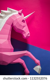 Head of a unicorn of paper on a pink and blue background. Geometry, pastel colors.