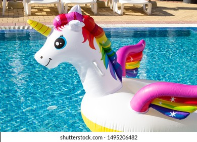 Head of unicorn swim tube on pool background. Summer holidays, beach vacation. Fantasy swim ring. Copyplace, place for text
