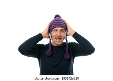 Head in warm hat. Handsome cheerful smiling man put knitted hat with pompom on. Fashion concept. Winter clothes and accessories. Mature emotional guy touching his head white background. Feeling good.