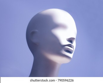 Head of a white mannequin on a blue background. Faceless girl.