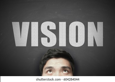 Head with white text Vision against blackboard background.
