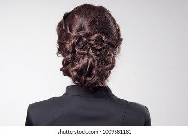 head of woman with brown hair in bun on gray isolated background rear view
