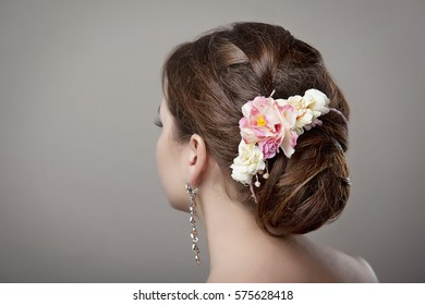 head of woman with hair in bun on gray isolated background