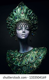 Head of woman mannequin in green decorated headwear, dark studio background