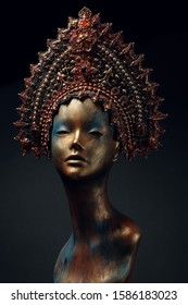 Head of woman mannequin in red decorated head wear, black studio background