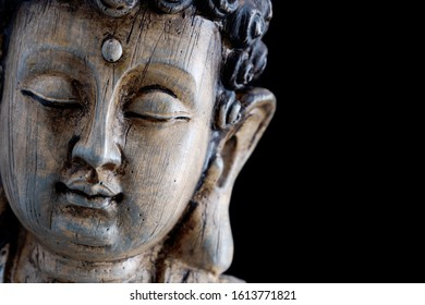 Head of a wooden Buddha sculpture isolated on black background