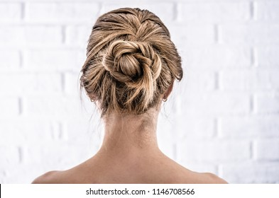 Head of a young woman from behind. Rear view braid hairdo. Hair bun