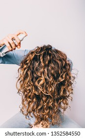 Head of young woman with long curly hair is lowered down to apply cosmetic care product. Female using spray with sea salt to make beachy waves hairstyle.