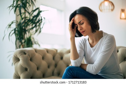 Headache. Close-up photo of a young woman, who is sitting on a sofa with her eyes closed, touching her head while suffering from a migraine.