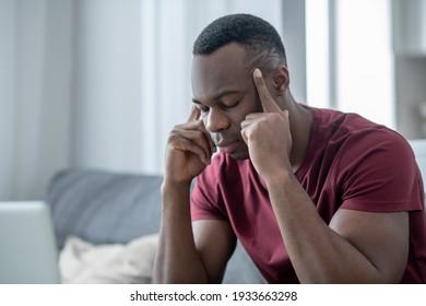 Headache. A dark-skinned young man suffering from a headache