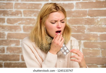 Headache and fever remedies. Woman tousled hair scarf hold glass water and tablets blister. Take medications to reduce fever. Girl feels ill suffer fever and take medicine. Pills for breaking fever.