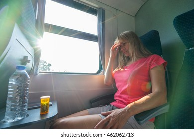 Headache and motion sickness. Stressed and tired young woman sitting near the window and with bottle of water and tablets on table while travelling by train.