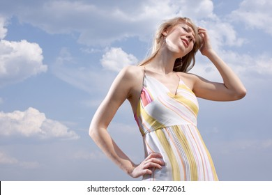 Headache on a hot sun - outdoor portrait on a cloudy sky background