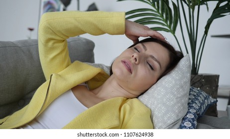 Headache, Tense Woman Laying on Sofa at Home